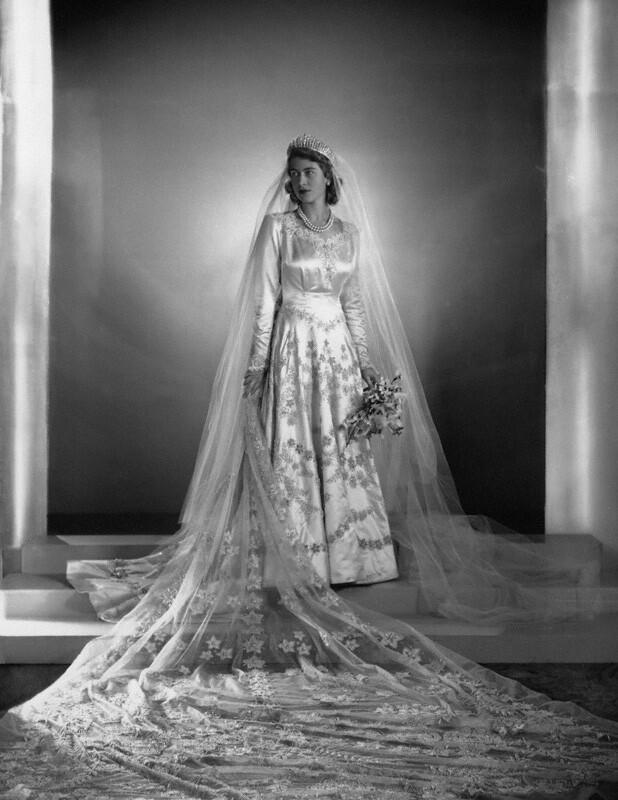 Платье Елизаветы II было вдохновлено работами Боттичелли, ивыполнено изсатина цвета слоновой кости стюлем ицветочной вышивкой серебряной нитью. Образ был дополнен фатой счетырехметро...