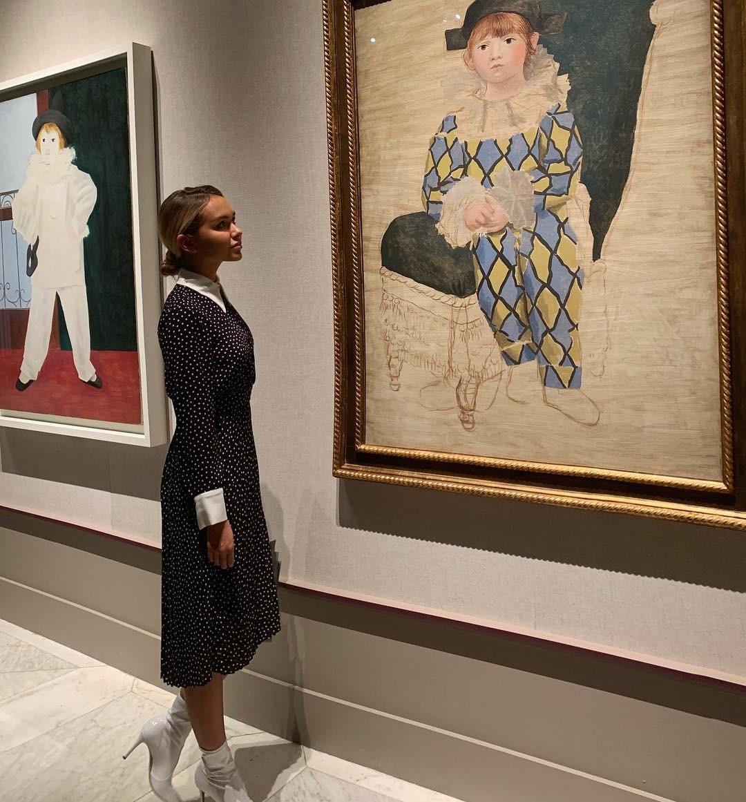 Для похода в музей Стеша Маликова выбрала черное платье длины миди в горох с кипенно-белыми манжетами и воротничком, а также белые ботильоны на тонком каблуке. Волосы девушка убрала в низ...
