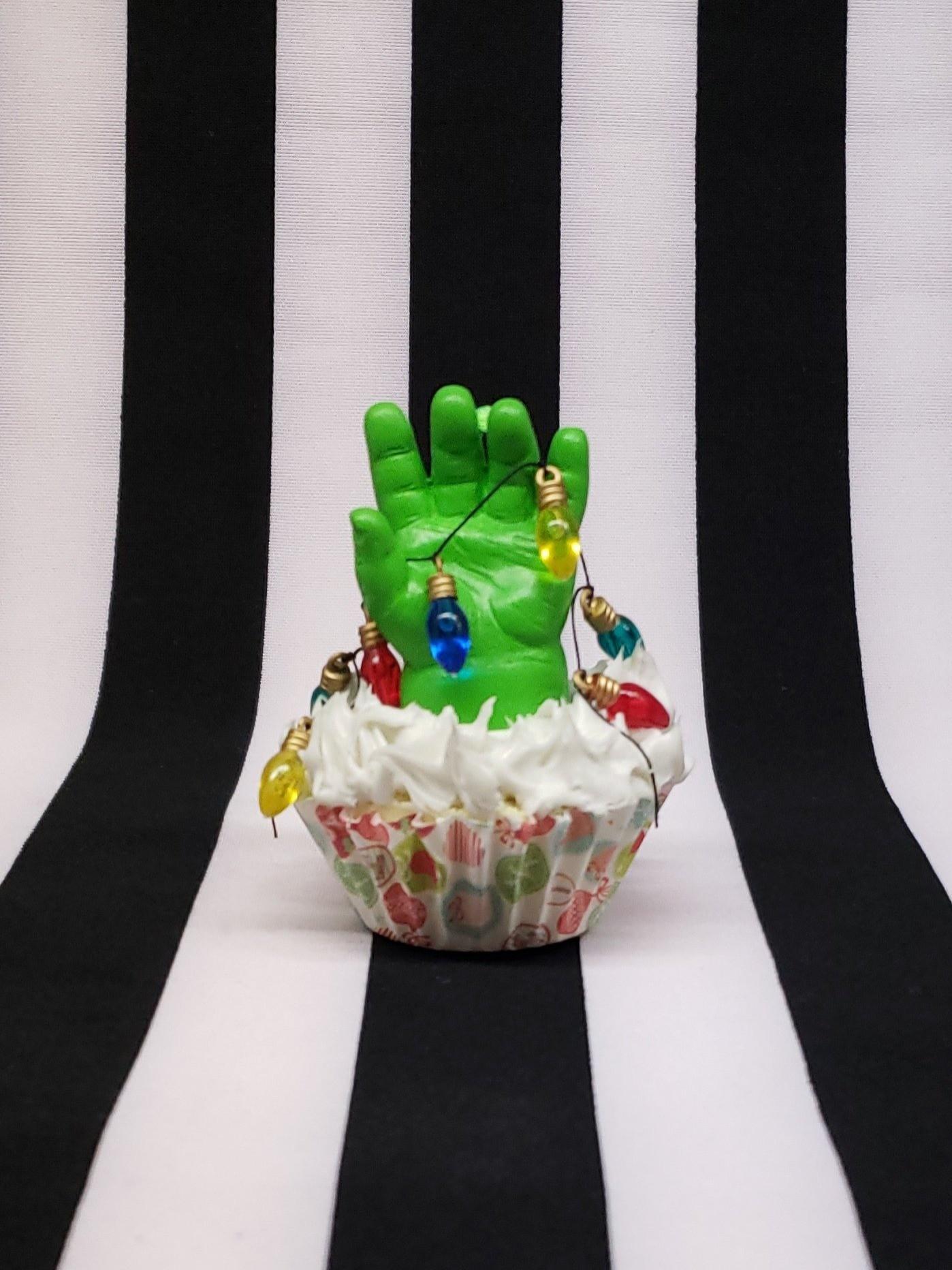 Как тебе такое украшение для стола – мощная рука зомби, которая разрывает капкейк изнутри? Разноцветные лампочки придают этому украшению веселое новогоднее настроение. Повесь его на самое...