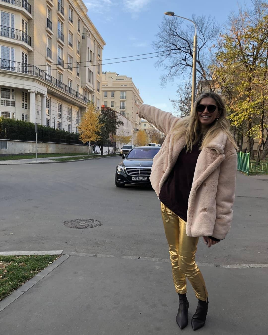 Для будничного осеннего дня Вера Брежнева выбрала дубленку средней длины из искусственного меха (настоящий тренд сезона), узкие брюки золотистого цвета и невероятно стильные черные матовы...