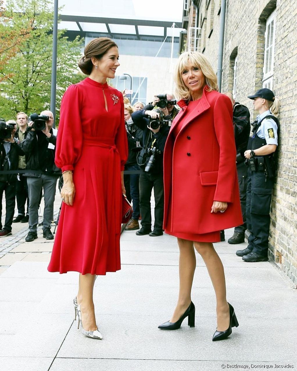 Первая леди Франции выбрала приталенное платье ярко-красного цвета (оттенок смотрится очень благородно!), легкое пальто втон, напоминающее пофасону жакет, ичерные лодочки надовольно в...