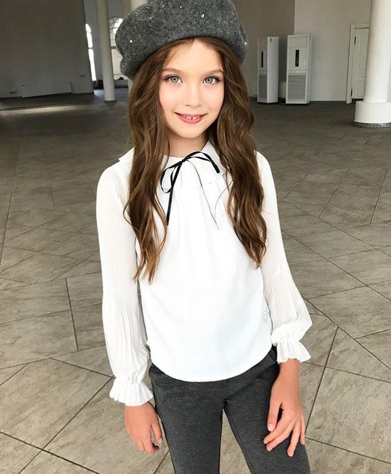 Белая хлопковая рубашка - неотъемлемая часть базового школьного гардероба ребенка. Но даже белая рубашка может смотреться стильно иинтересно. Длядевочки подбирай блузы ирубашки сманже...