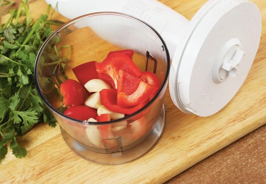 Чеснок и сладкий перец измельчить в блендере. Кинзу вымыть, обсушить и мелко нарезать.