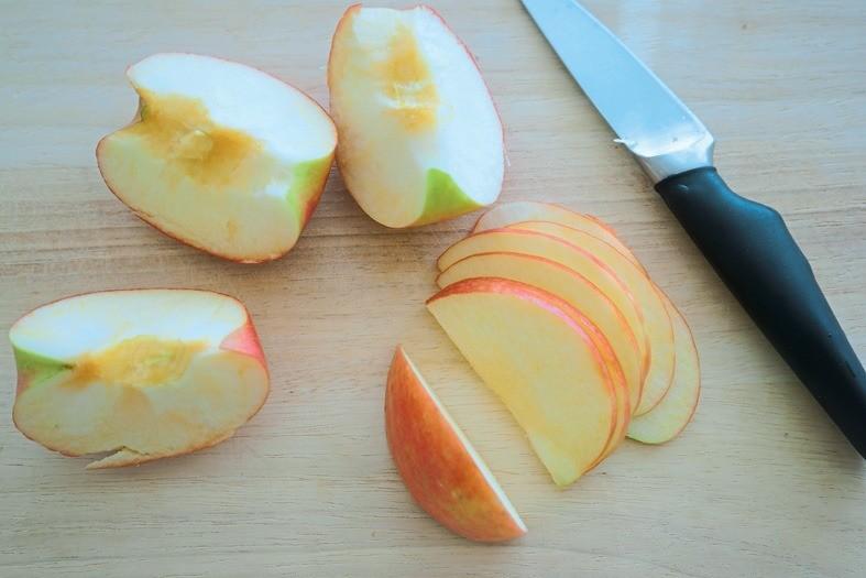Помытые яблоки разрежь на4 части, удали сердцевину. Тонко нарежь. Чтобы ломтики стали эластичными, поставь их на1 минуту вмикроволновку.
