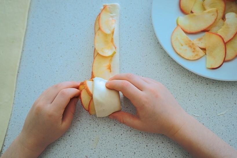 Накрой яблоки тестом ивыложите второй слой яблочных ломтиков. Скрути рулончик. Лучше положить яблочные розы внебольшие формы для выпекания.