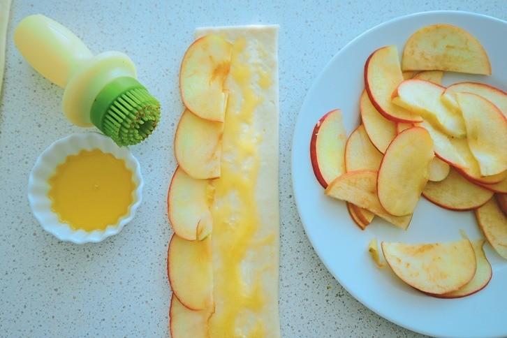 Смажь полоску жидким медом. Накрай теста выложи ломтики яблока повсей длине. Наэтом этапе можно добавить корицу.