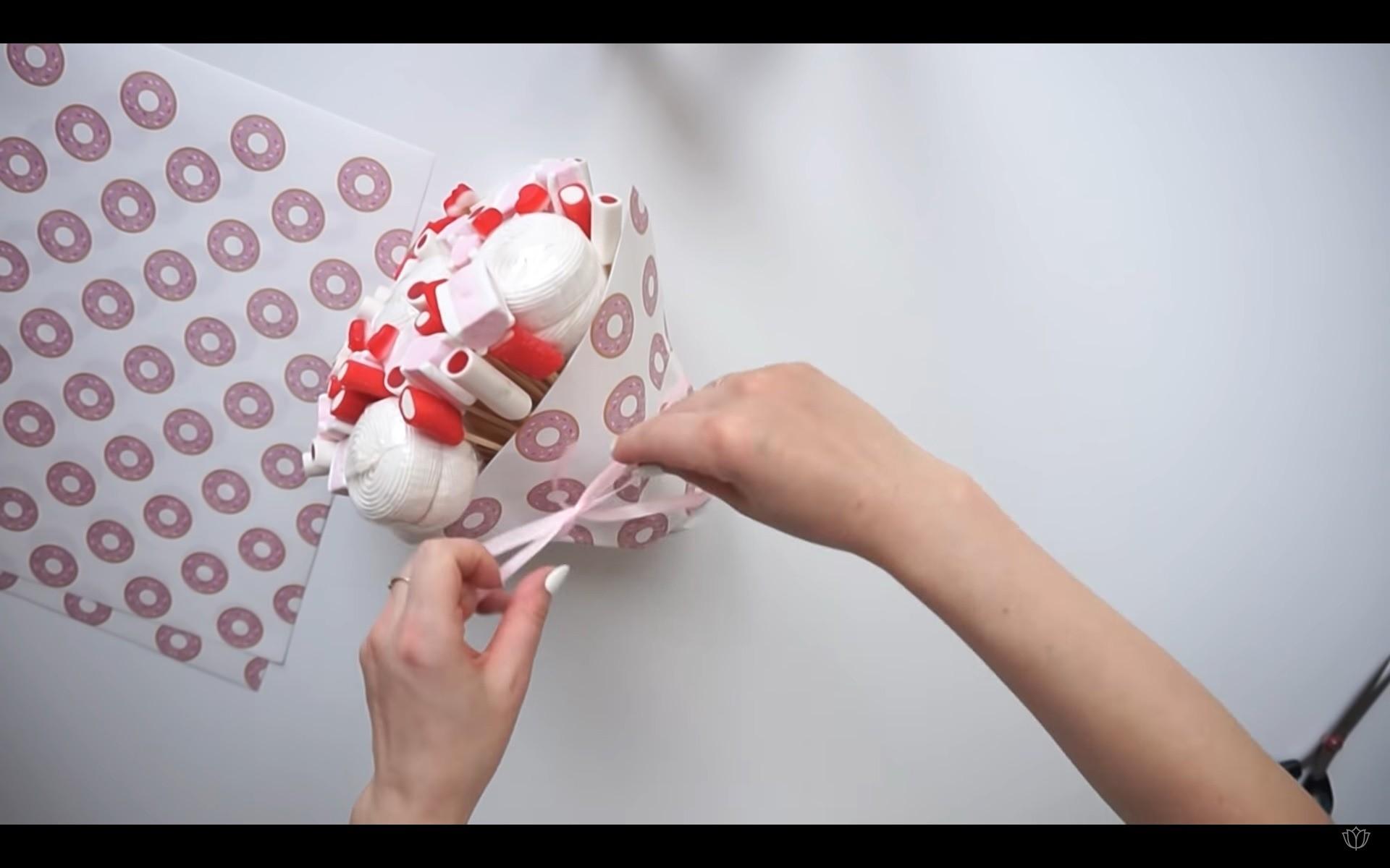 Аккуратно придай бумаге необходимую форму букета изафиксируй первый слой обертки припомощи ленты.