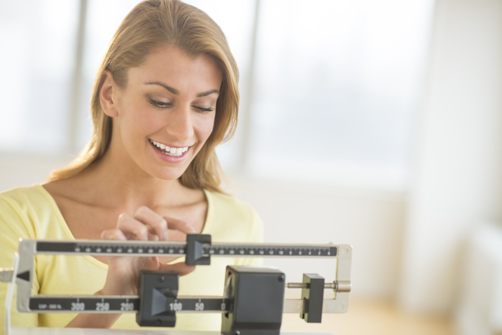 Happy young woman weighing herself on balance scale at health club