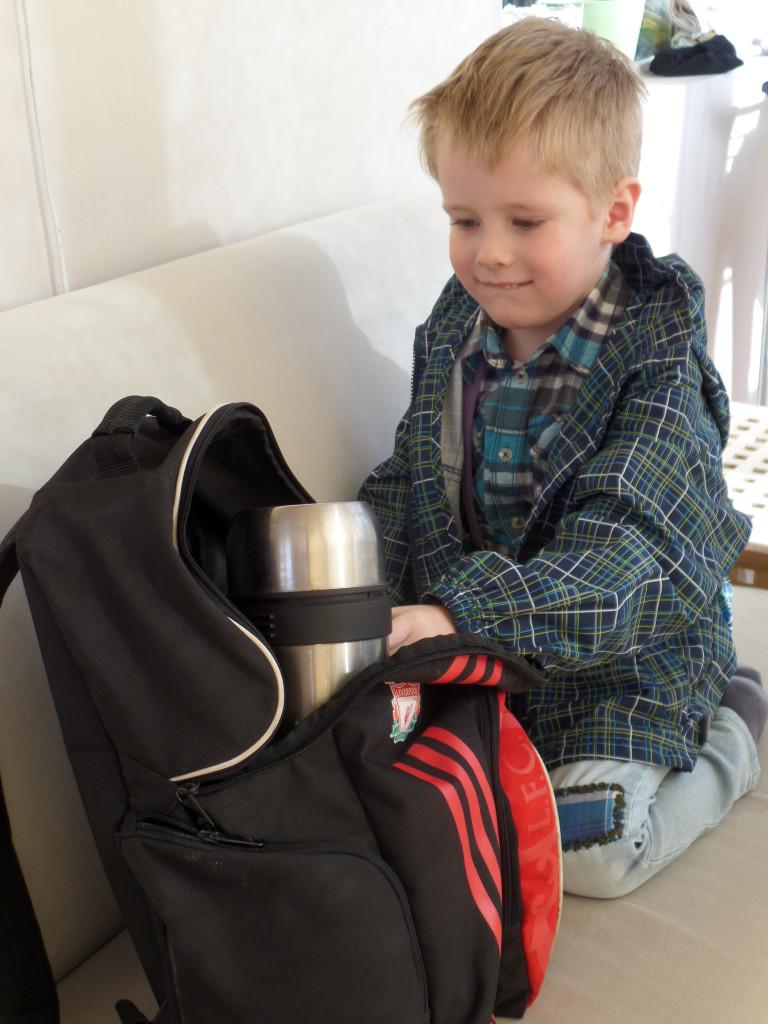 Ребенок складывает вещи в рюкзак